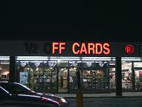 Store sign, half off cards, not fully illuminated.