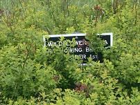 Sign overgrown with weeds.