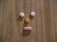 Vitamin tablets arranged as a smiley face.